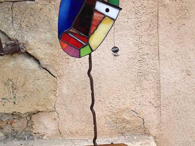 Máscara en vidrio de colores mediante la técnica Tiffany sobre peana de metal y madera. 38€
